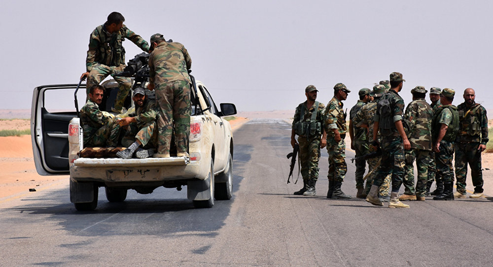 Syrian government forces gather on a road in Bir Qabaqib, more than 40 kilometres west of Deir Ezzor, after taking control of the area on their way to Kobajjep in the ongoing battle against Islamic State (IS) group jihadists on September 4, 2017