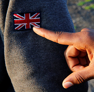 An Ethiopian migrant named Ermias (16 years old) points at an Union Jack patch as he waits on line during a food distribution near the former jungle in Calais, France, August 23, 2017