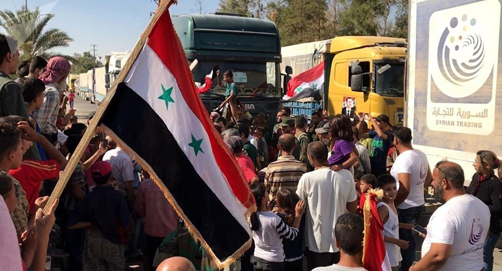 Deir ez-Zor residents welcome a truck convoy of medicines and food. File photo