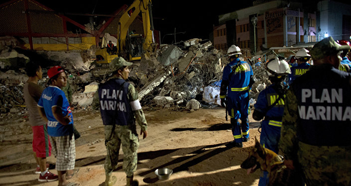 Rescuers sift through the rubble of the partially collapsed city hall in Juchitan , Oaxaca state, Mexico, following a massive earthquake, Friday, Sept. 8, 2017