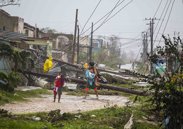 Residents walk near downed power lines felled by Hurricane Irma, in Caibarien, Cuba, Saturday, Sept. 9, 2017
