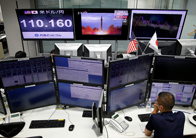 An employee of a foreign exchange trading company works in front of monitors showing TV news on North Korea's missile launch (top C) and the Japanese yen's exchange rate against the U.S. dollar (top L) in Tokyo, Japan, September 15, 2017