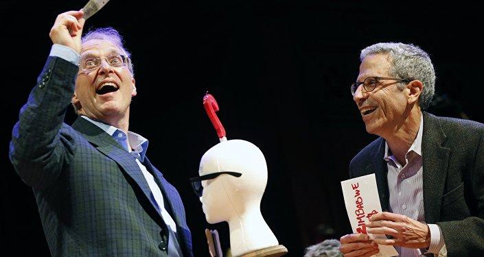 James Heathcote, left, reacts after receiving the Ig Nobel Anatomy Prize from Nobel laureate Eric Maskin (economics, 2007) during ceremonies at Harvard University in Cambridge, Mass