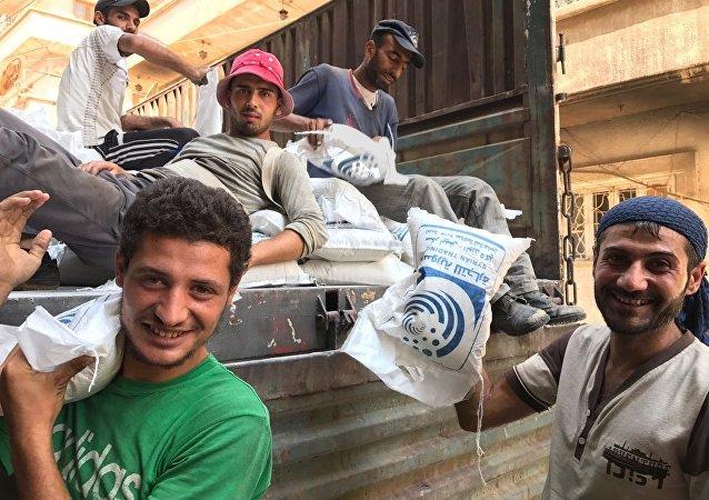 Men unload a van with sugar in Deir ez-Zor.