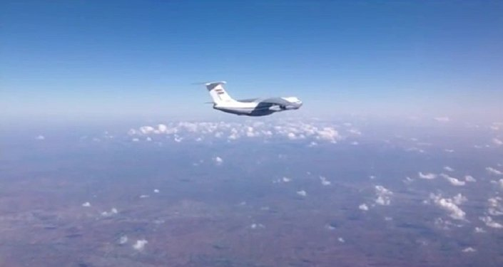 Syrian Air Force aircraft before dropping humanitarian cargo on Russian parachute platforms in the area of Deir ez-Zor, Syria. (A snap shot from the video published by the Russian Defense Ministry at its official YouTube channel.