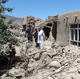 Afghan villagers gather near a destroyed house in Logar province, south of Kabul, Afghanistan (File)