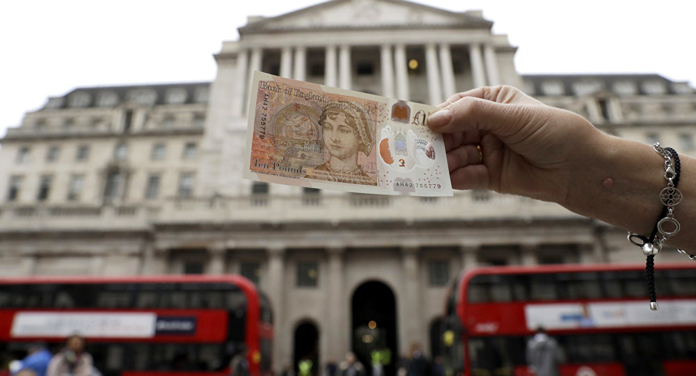 One of the new British 10 pound notes is posed for photographs outside the Bank of England in the City of London.