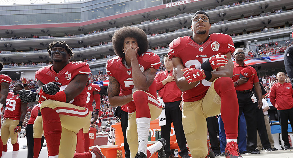 from left, San Francisco 49ers outside linebacker Eli Harold, quarterback Colin Kaepernick and safety Eric Reid kneel during the national anthem before an NFL football game against the Dallas Cowboys in Santa Clara, Calif. Since Kaepernick announced he would not stand for the song in protest of racial discrimination against blacks in the United States, many performers are now rethinking offers to sing the national anthem.