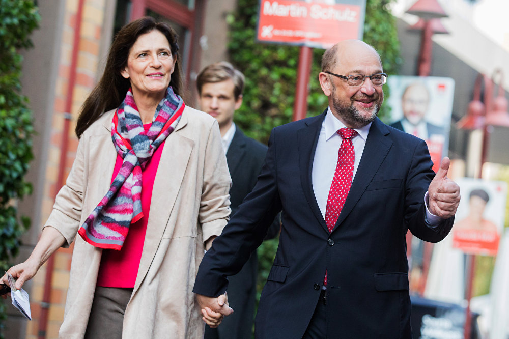Martin Schulz, leader of Germany's social democratic party SPD and candidate for Chancellor, and his wife Inge Schulz arrive to cast their ballots at a polling station in Wuerselen, western Germany, during general elections on September 24, 2017