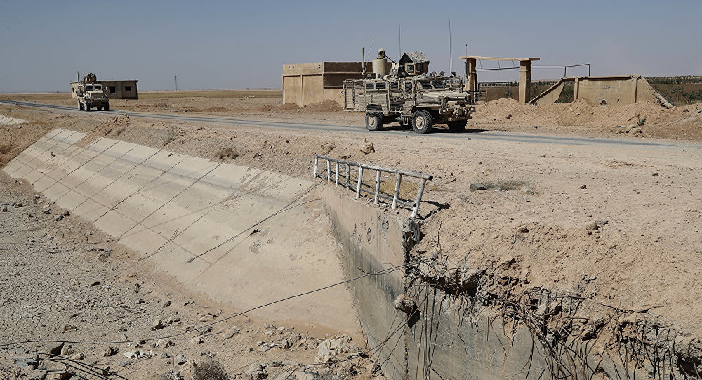 U.S. armored vehicles past near a destroyed bridge on a road that links to Raqqa city, northeast Syria. (File)