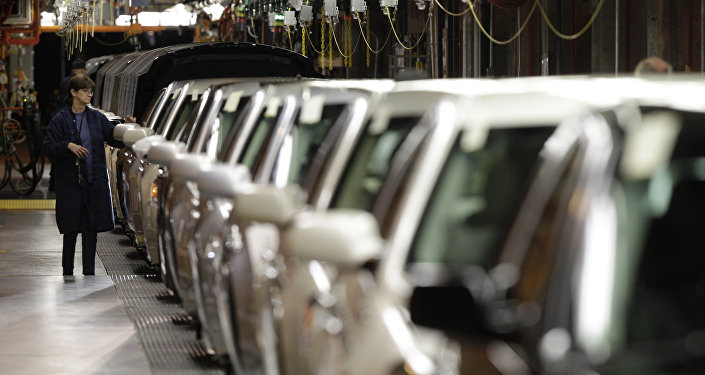 In this Nov. 30, 2010 file photo, a line worker checks vehicles at the General Motors Hamtramck assembly plant in Hamtramck, Mich.