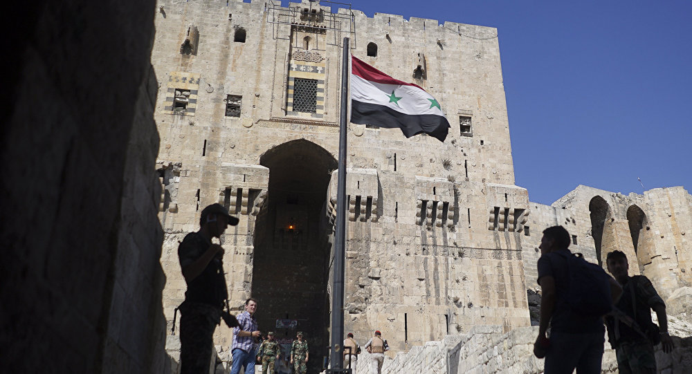 People walk into the Citadel, Aleppo's famed fortress where much of the fierce fighting took place in 2016, in Syria, Tuesday, Sept. 12, 2017