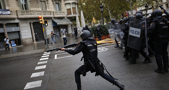 Spanish riot police shoots rubber bullet straight to people trying to reach a voting site at a school assigned to be a polling station by the Catalan government in Barcelona, Spain, Sunday, 1 Oct. 2017. Spanish riot police have forcefully removed a few hundred would-be voters from several polling stations in Barcelona.