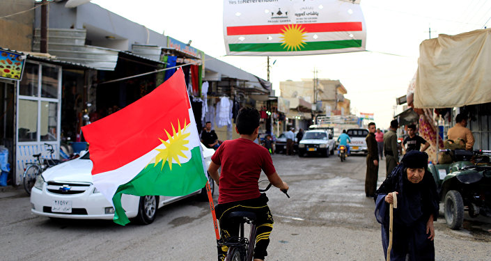 A boy rides a bicycle with the flag of Kurdistan in Tuz Khurmato, Iraq September 24, 2017