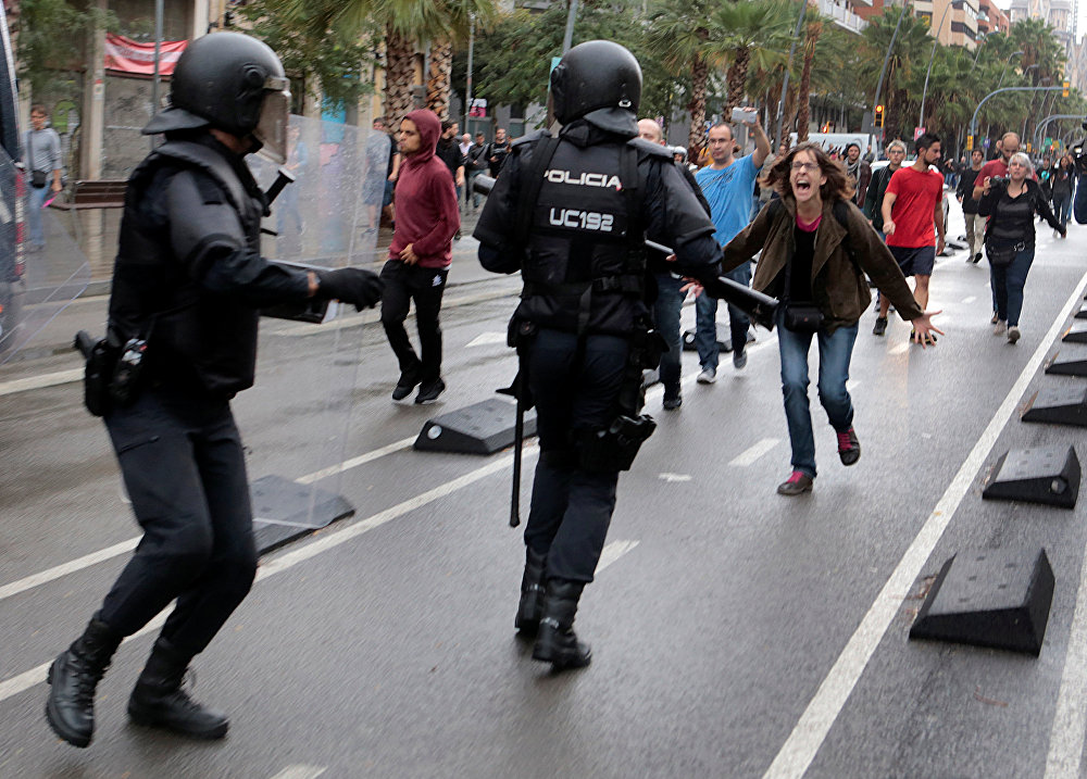 A woman yells at riot police near a a polling station for the banned independence referendum in Barcelona, Spain, October 1, 2017