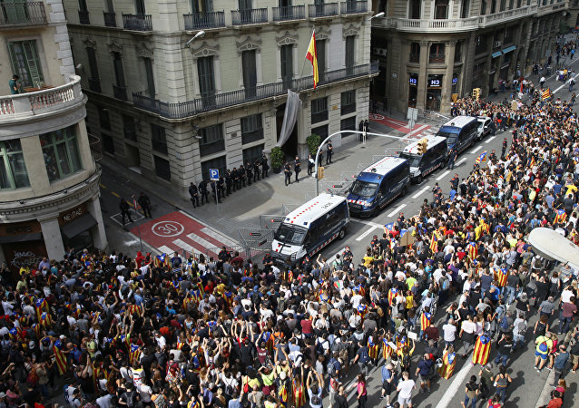 Catalan regional mossos d'esquadra police vans form a protective barrier between protesters and the national police headquarters during a one-day strike in Barcelona, Spain
