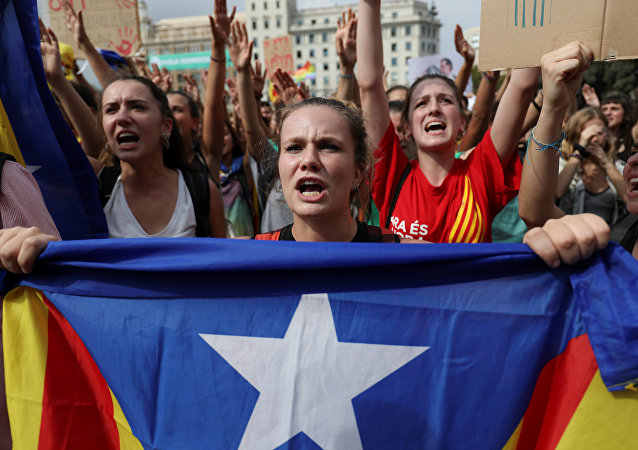 A woman holds up an Estelada (Catalan separatist flag) during a protest one day after the banned independence referendum in Barcelona, Spain