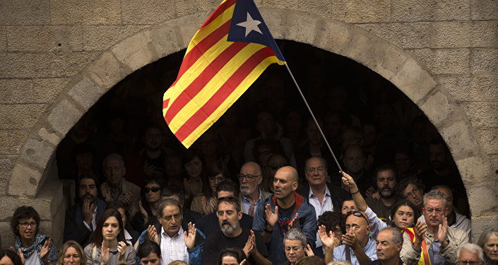 Catalan independence supporters, one waving an estelada, or Catalonia independence flag, applaud during a rally outside the city hall of Girona, Spain