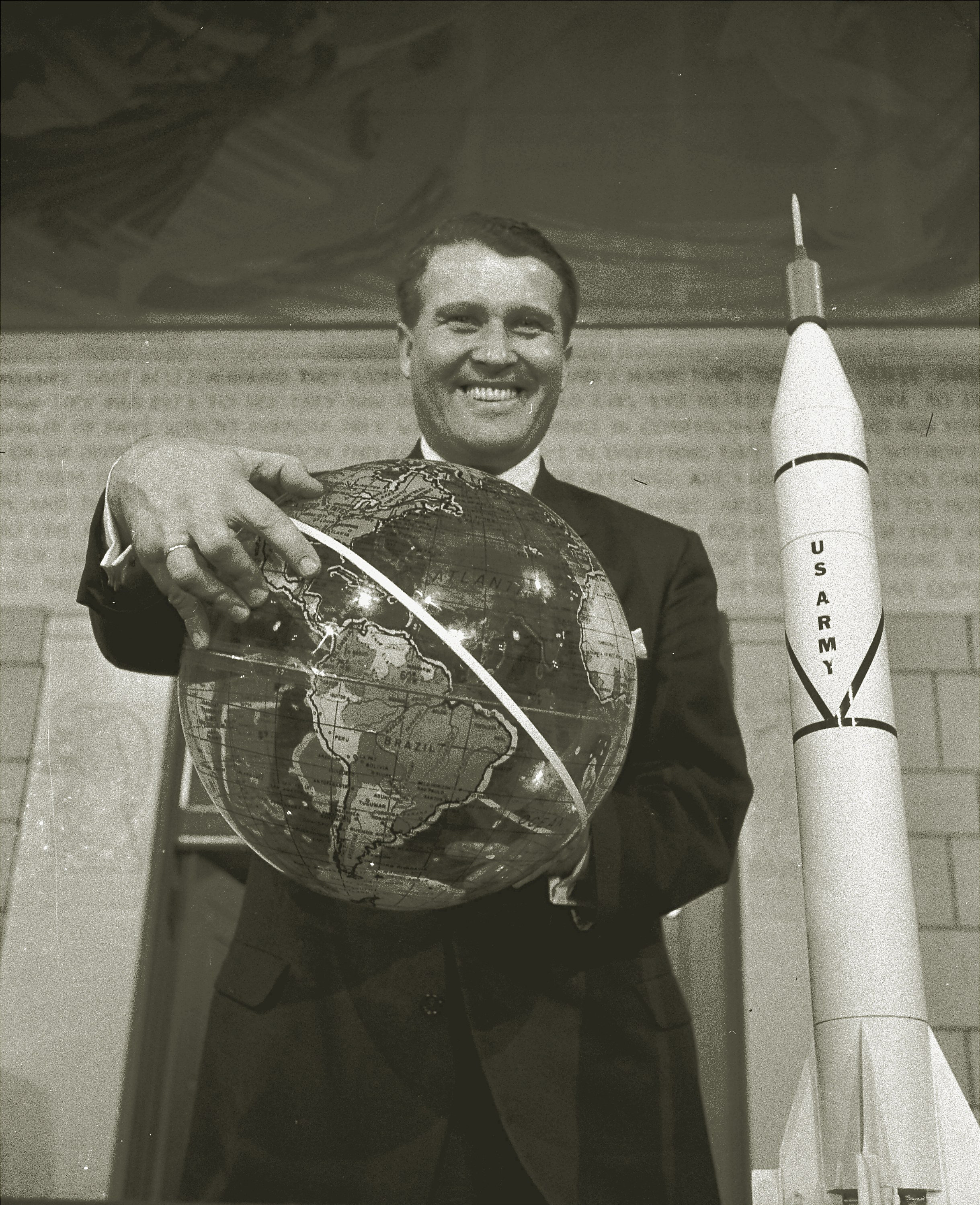 Dr. Wernher Von Braun, chief of the army ballistic missile agency's development operations, grins in Washington February 1, 1958, as he holds a globe marked with one path of the U.S. satellite. (File)