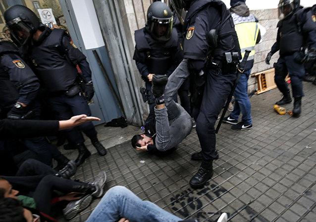 Spanish police officers drag a man as they try to disperse voters arriving to a polling station in Barcelona, on October 1, 2017 during a referendum on independence for Catalonia banned by Madrid
