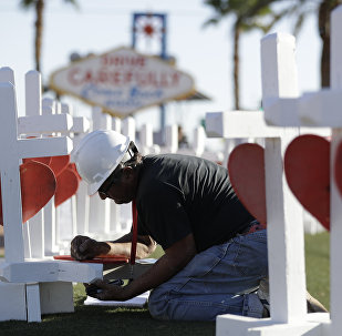 Greg Zanis writes the name of a victim of Sunday's mass shooting as he places crosses near the city's famous sign Thursday, Oct. 5, 2017, in Las Vegas.