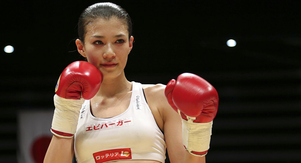 Japan's Tomomi Takano poses for photographers after defeating her compatriot Hisami Oishi in their women's super flyweight four-round boxing match in Tokyo. (File)