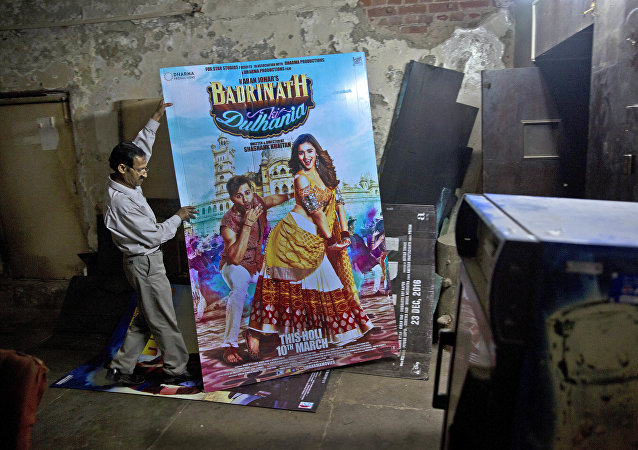 In this Tuesday, March 28, 2017 photo, an employee places a poster of a Bollywood film in the dump room of Regal Theater in New Delhi, India