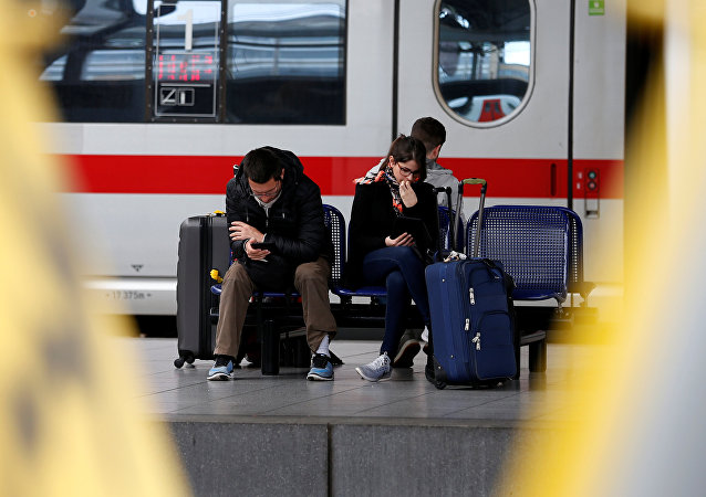 Passengers sit on a bench as they wait for a train during a strike of public transport service at Midi/Zuid railway station in Brussels, Belgium
