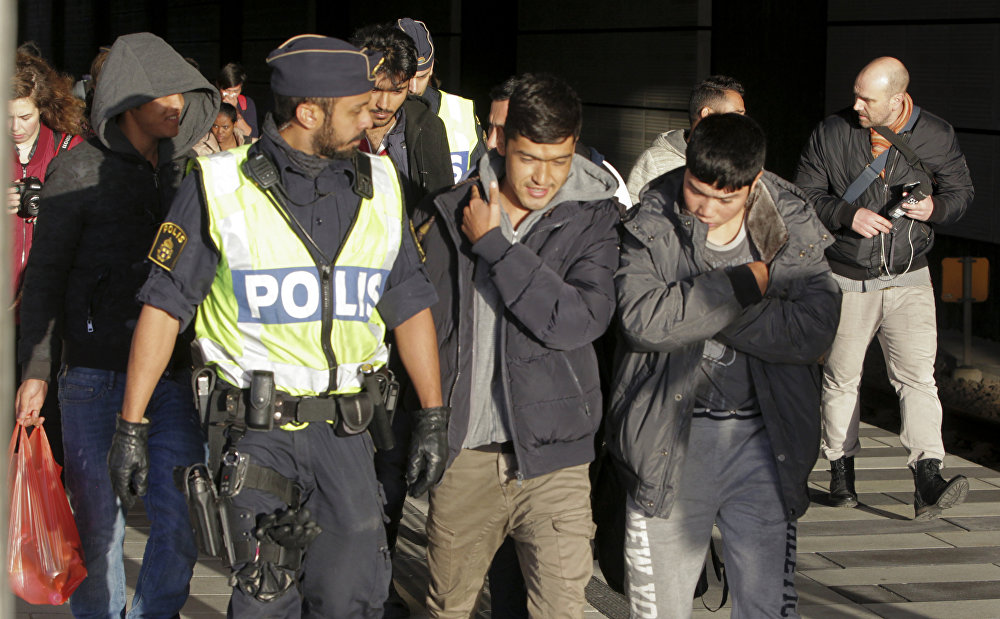 A group of migrants off an incoming train walk down a platform as they are accompanied by the police at the Swedish end of the bridge between Sweden and Denmark near Malmoe on November 12, 2015.