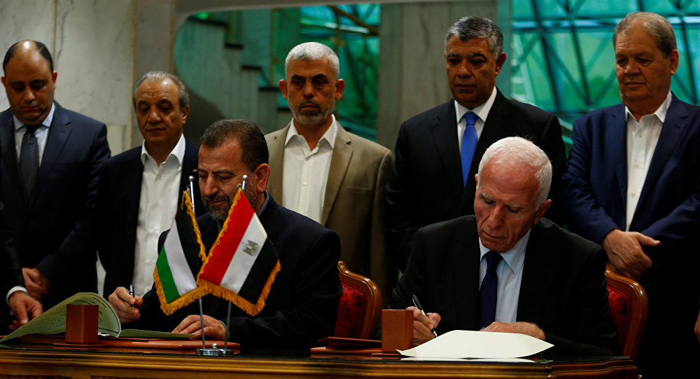 Head of Hamas delegation Saleh Arouri and Fatah leader Azzam Ahmad sign a reconciliation deal in Cairo, Egypt