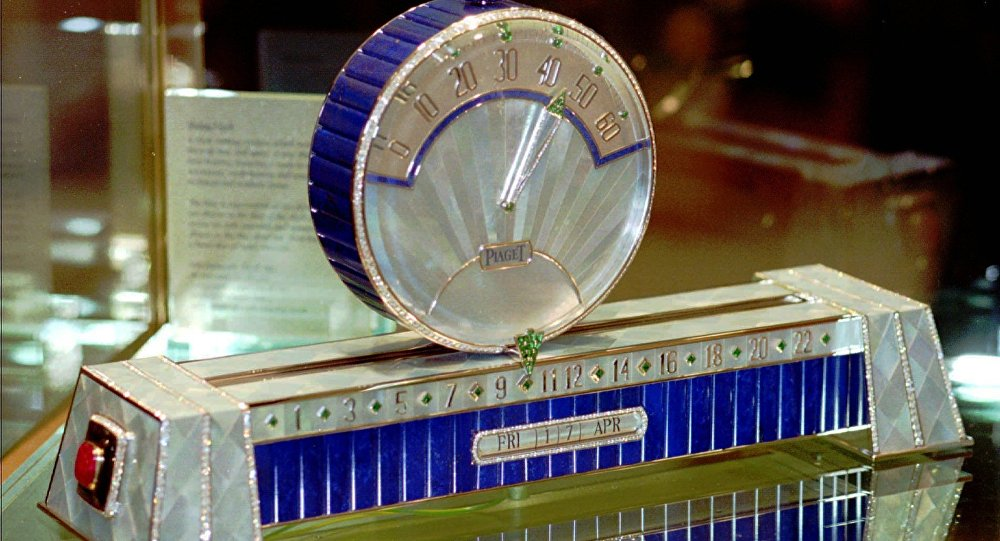 Swiss watch manufacture Piaget with the only model of the Sliding Clock at the 1998 International Fine Watchmaking Exhibition at Geneva, Switzerland. The hours are shown at the base of the clock and the minutes are shown on the disc sliding above the base. The price of these clock, with 926 diamonds (53,27 cts), 50 emeralds (11.63 cts), two rubies, gold weight 930 grams, is some $1.572 million.