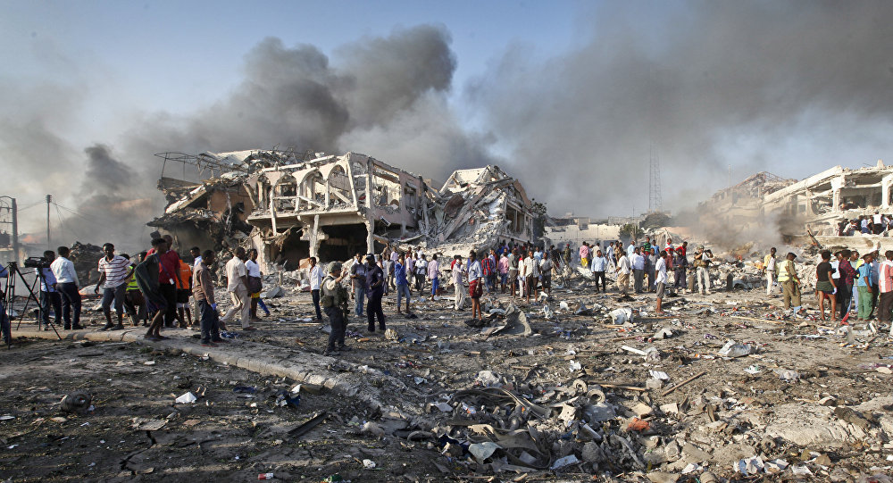 Somalis gather and search for survivors by destroyed buildings at the scene of a blast in the capital Mogadishu, Somalia, Saturday, Oct. 14, 2017