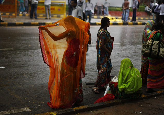 An Indian woman adjusts her sari after she got wet in the monsoon rains in New Delhi, India, Wednesday, Aug. 7, 2013