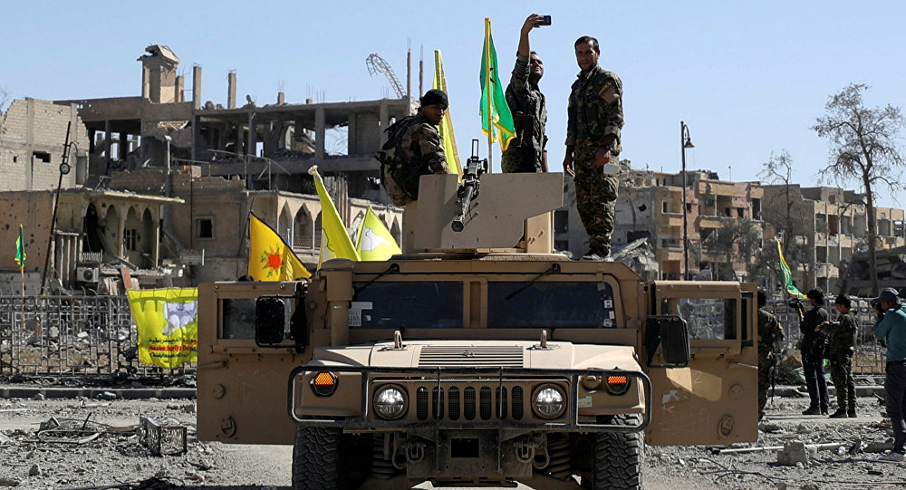 A Fighter of Syrian Democratic Forces takes a selfie as he stands on a military vehicle in Raqqa, Syria October 17, 2017