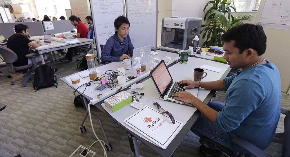 In this Thursday, June 30, 2016 photo, Babson College graduate school alumnus Abhinav Sureka, of Mumbai, India, right, types in his work space at the college in Wellesley, Mass.