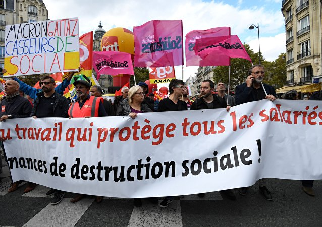 People hold a banner reading a work which protects all the employees during a demonstration called by the CGT workers' union against the French president's labour law reforms, on October 19, 2017 in Paris
