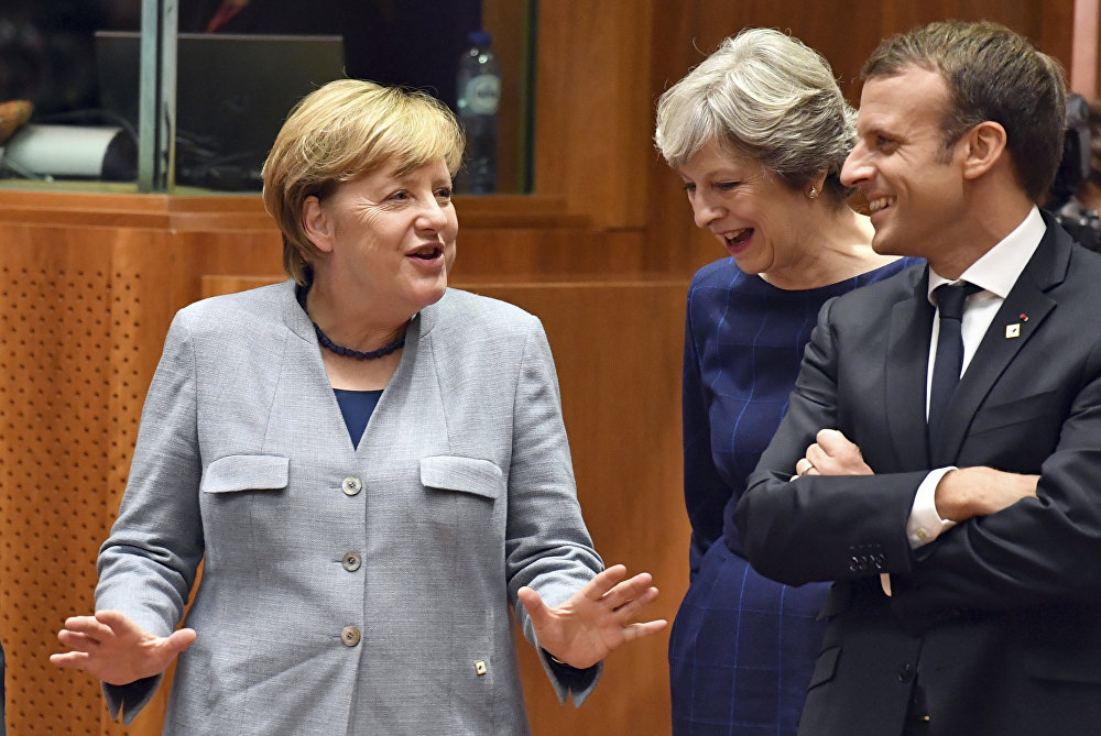 German Chancellor Angela Merkel, left, speaks with British Prime Minister Theresa May, center, and French President Emmanuel Macron prior to a round table meeting at an EU summit in Brussels on Thursday, Oct. 19, 2017.