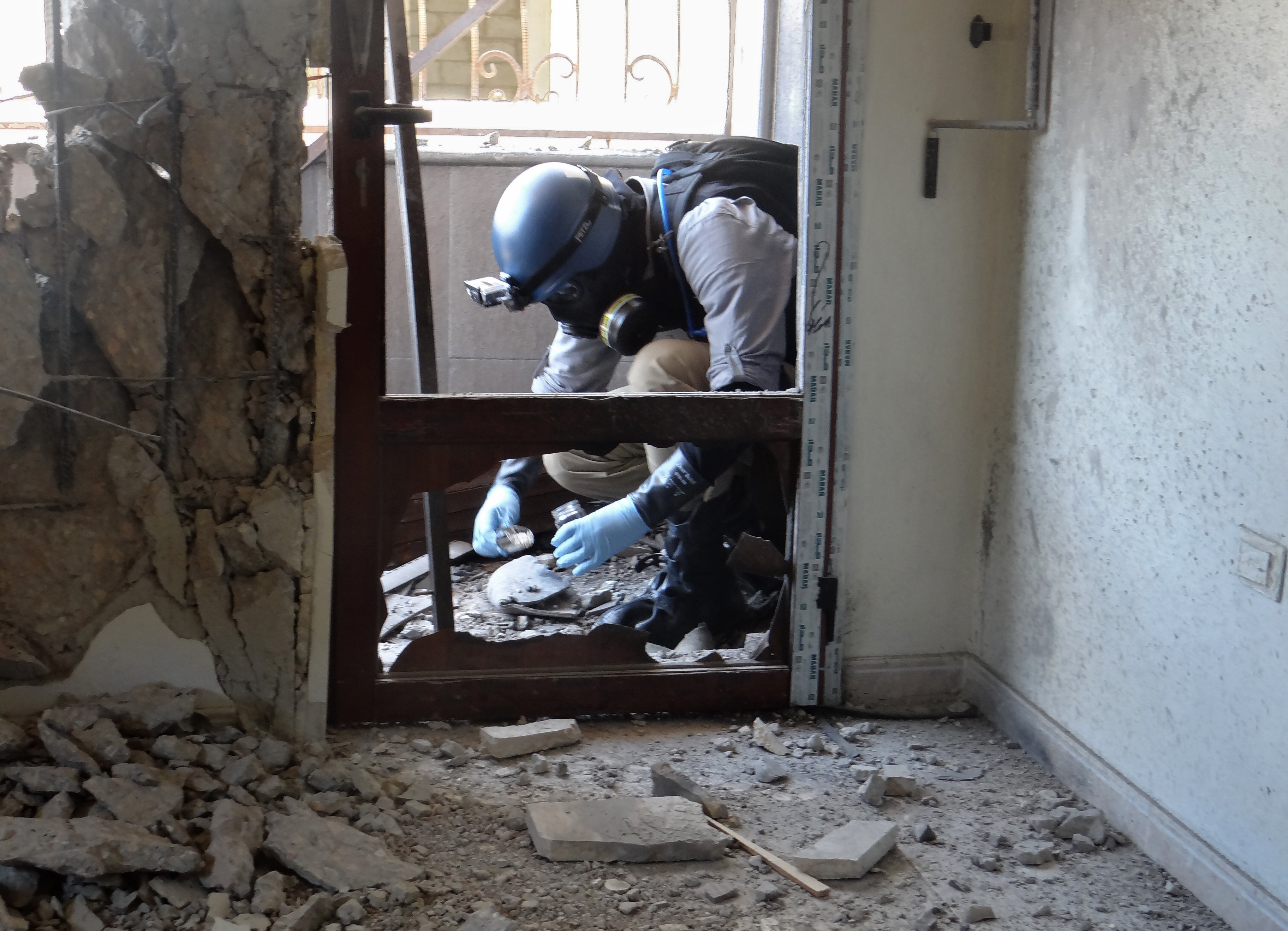 A United Nations (UN) arms expert collects samples, as he inspect the site where rockets had fallen in Damascus' eastern Ghouta suburb during an investigation into a suspected chemical weapons strike near the capital (File)