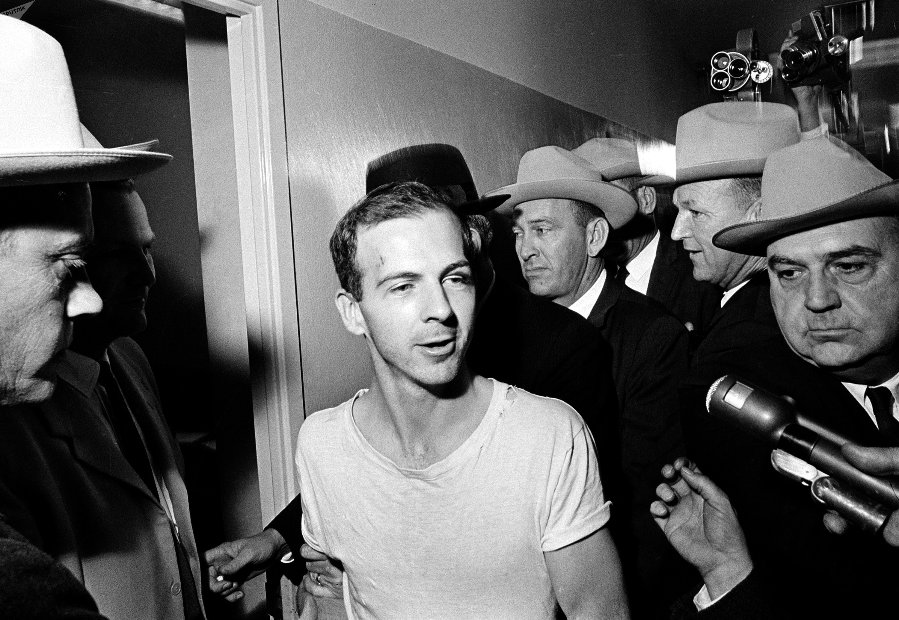 Surrounded by detectives, Lee Harvey Oswald talks to the press as he is led down a corridor of the Dallas police station for another round of questioning in connection with the assassination of US President John F. Kennedy, November 23, 1963.
