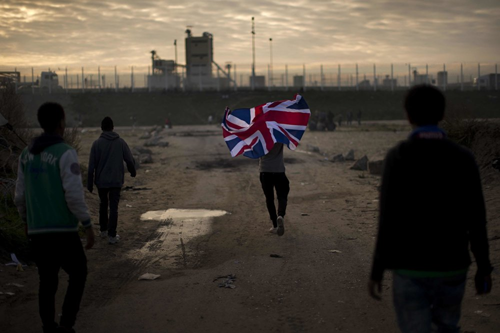 In this Tuesday, Oct. 25, 2016 file photo a man runs with a British flag inside a makeshift camp known as the jungle near Calais, northern France.