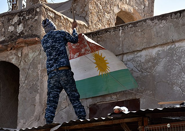 An Iraqi soldier removes a Kurdish flag from Altun Kupri on the outskirts of Irbil, Iraq, Friday Oct. 20, 2017
