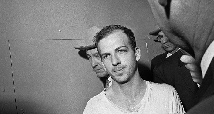 In this Nov. 23, 1963 file photo, Lee Harvey Oswald is led down a corridor of the Dallas police station for another round of questioning in connection with the assassination of US, President John F. Kennedy. Oswald, who denied any involvement in the shooting, was formally charged with murder.