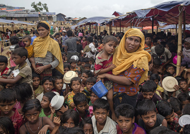 Rohingya Muslims, who crossed over from Myanmar into Bangladesh, wait for their turn to receive food handouts distributed to children and women by a Turkish aid agency at Thaingkhali refugee camp, Bangladesh, Saturday, Oct. 21, 2017