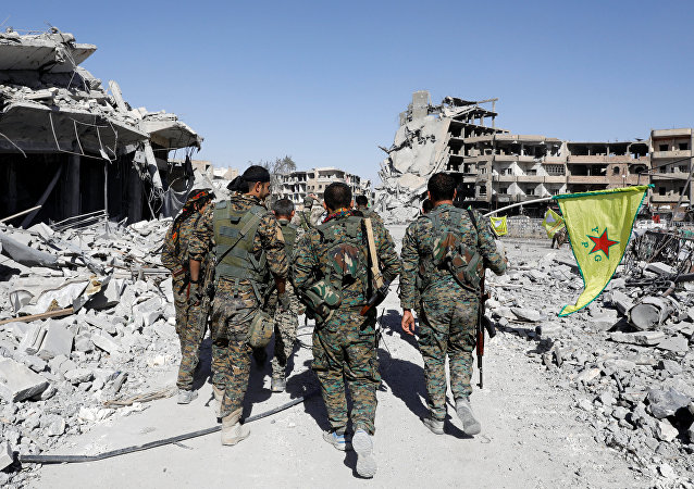 Fighters of Syrian Democratic Forces walk past the ruins of destroyed buildings near the National Hospital after Raqqa was liberated from the Islamic State militants, in Raqqa, Syria October 17, 2017. Picture taken October 17, 2017