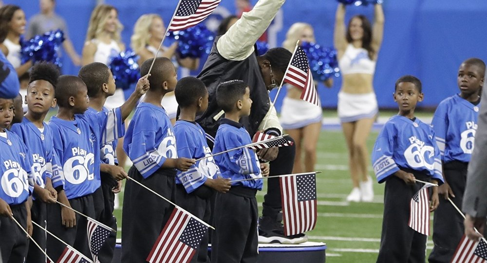 In a file photo from Sept. 24, 2017, National anthem singer Rico Lavelle bends to his knee, bows his head and raises his fist after singing the anthem before the first half of an NFL football game between the Detroit Lions and the Atlanta Falcons in Detroit. The sight of football players kneeling during the national anthem is the continuation of a tradition nearly as old the song itself. University of Michigan musicology professor Mark Clague says The Star-Spangled Banner has been a channel for protest since at least the 1840s. The lyrics were recast as an anti-slavery song and it's been used or reworked to push for racial equality, women's suffrage, prohibition and labor rights.