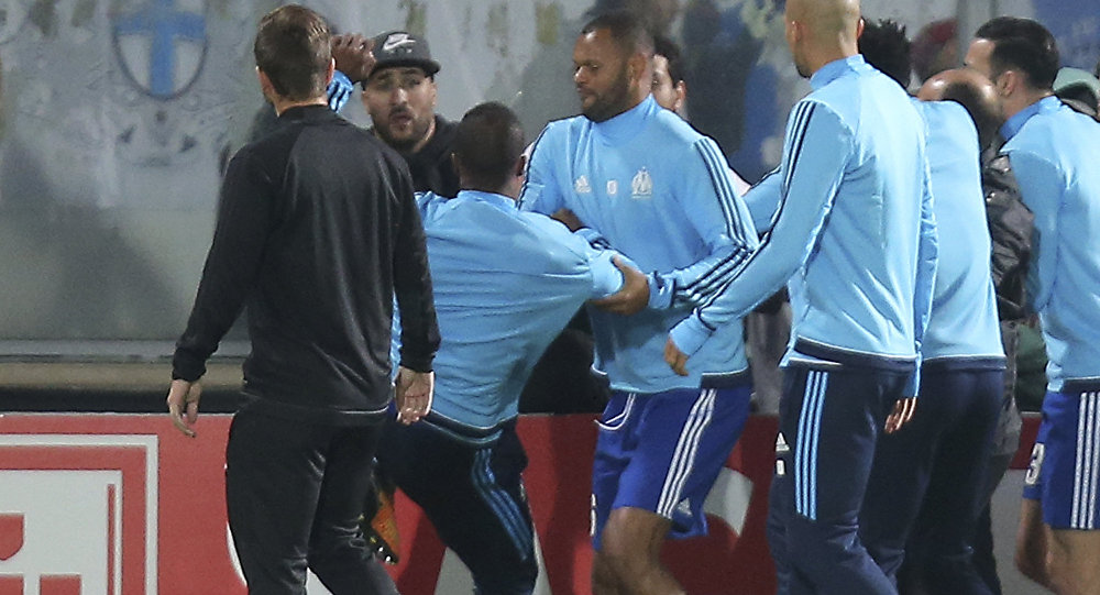Marseille's Patrice Evra, third left, raises his foot trying to kick a man during a scuffle with Marseille supporters who trespassed into the field before the Europa League group I soccer match between Vitoria SC and Olympique de Marseille at the D. Afonso Henriques stadium in Guimaraes, Portugal, Thursday, Nov. 2, 2017.
