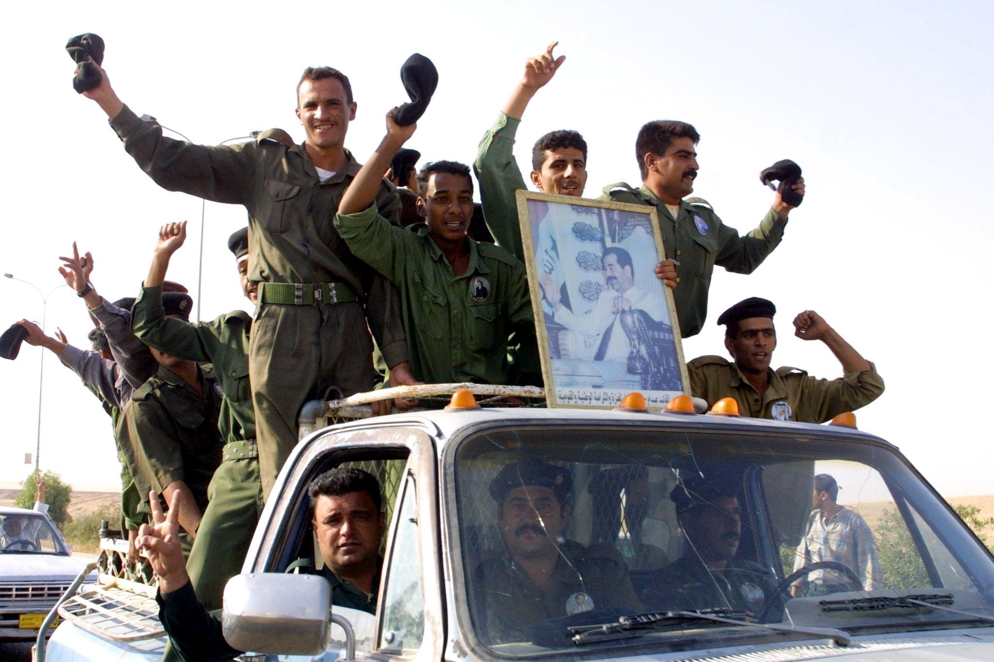 Iraqi soldiers celebrate 15 October 2002 on their way to vote in the presidential referendum in the city of Tikrit, Saddam Hussein's birthplace, some 170 kms north of the capital Baghdad