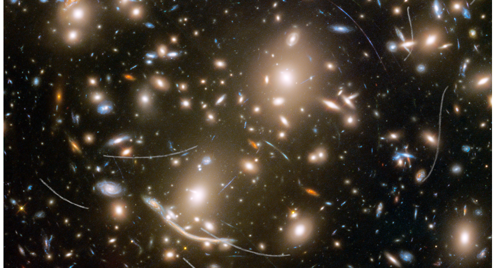 Galaxy cluster Abell 370 contains several hundred galaxies tied together by the mutual pull of gravity. It is located approximately 4 billion light-years away in the constellation Cetus, the Sea Monster. The thin, white trails that look like curved or S-shaped streaks are from asteroids that reside, on average, only about 160 million miles from Earth.