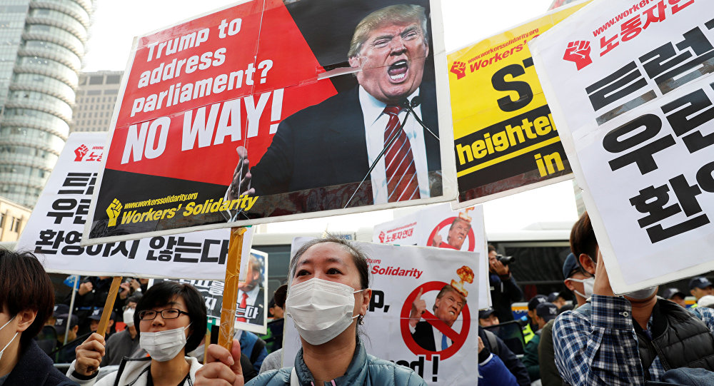 Protesters against U.S. President Donald Trump hold placards while waiting for Trump's motorcade to pass by in central Seoul, South Korea, November 7, 2017