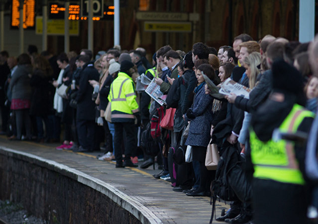 Commuters wait on a platform to catch a train toward central London